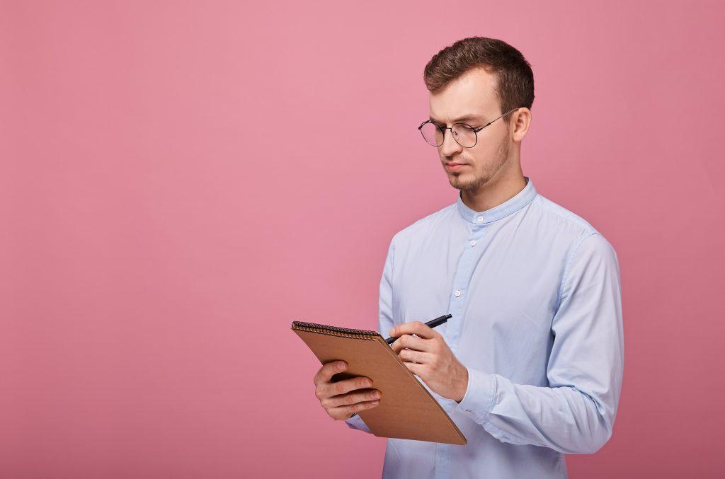 茶色のフリップチャートと黒のボールペンで眼鏡をかけた淡いブルーのシャツを着たクールな学生